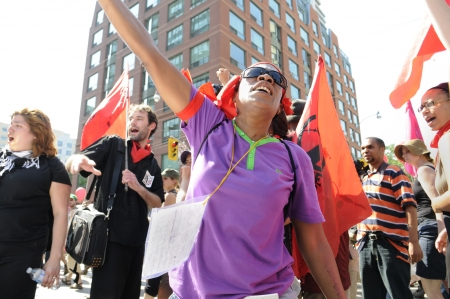 chanting: TORONTO-JUNE 25: An angry afro- american woman chanting slogans in front of a police vehicle during the G20 Protest on June 25, 2010 in Toronto, Canada.