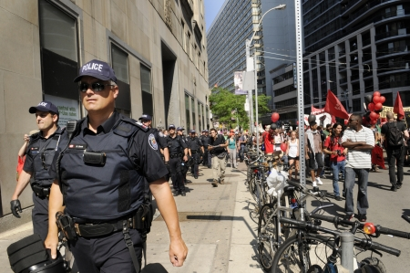 TORONTO-JUNE 25: Toronto police marching and protecting the sidewalks during the G20 Protest on June 25, 2010 in Toronto, Canada. Editorial