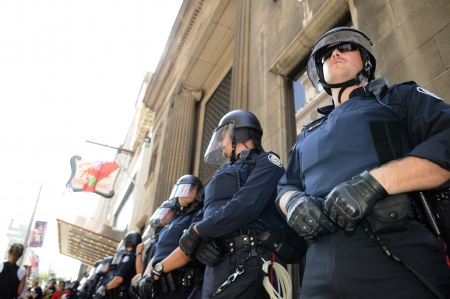 TORONTO-JUNE 25: Toronto Police officers in riot gear protecting a financial building during the G20 Protest on June 25, 2010 in Toronto, Canada.