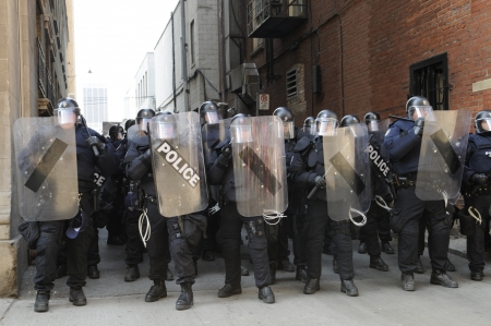 restricting: TORONTO-JUNE 25: Toronto Riot Police restricting protesters from entering an alley between two financial buildings during the G20 Protest on June 25, 2010 in Toronto, Canada.