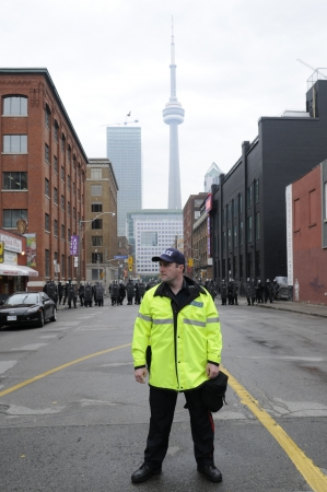 TORONTO-JUNE 26: A Toronto police officer standing in front of a perimeter formed by the riot police during the G20 Protest on June 26 2010 in Toronto, Canada. Stock Photo - 20263872