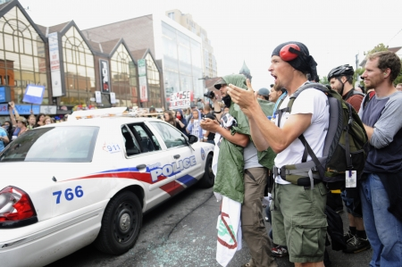 chanting: TORONTO-JUNE 26: Protesters chanting slogans and singing songs in front of a Toronto police vehicle during the G20 Protest on June 26 2010 in Toronto, Canada.