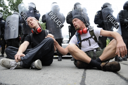 TORONTO-JUNE 26: Protesters singing while being sitted in front of the riot police during the G20 Protest on June 26 2010 in Toronto, Canada.