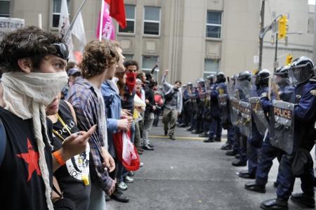 トロント-6 月 26 日: 抗議者は、2010 年 6 月 26 日に、カナダのトロントでの G20 の抗議中に暴動の警察官と向かい合って立ってください。 報道画像