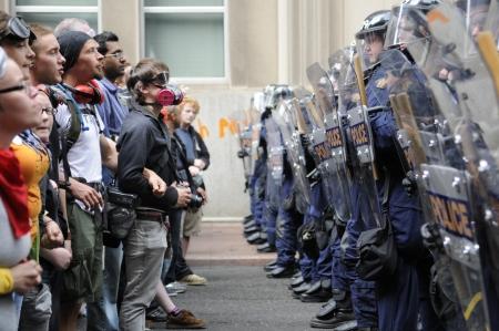 TORONTO-26 Juni: Toronto Riot Police (r) beschränken Demonstranten Eindringen von G20-Gipfel Bereich an der Metro Convention Centre am 26. Juni 2010 in Toronto, Kanada. Standard-Bild - 20263987