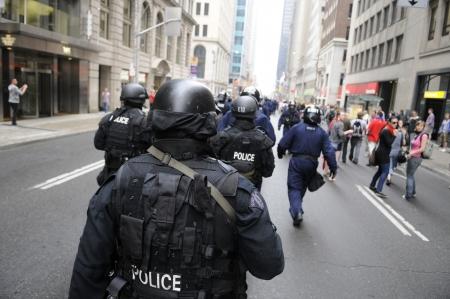 トロント-6 月 26 日: エリート暴動警察官トロント、カナダで 2010 年 6 月 26 日に G20 の抗議の間に通りを行進しています。