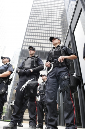 security helmet: TORONTO-JUNE 27: Toronto police officers standing in front of the TD Tower a major financial building during the G20 Protest on June 27, 2010 in Toronto, Canada. Editorial