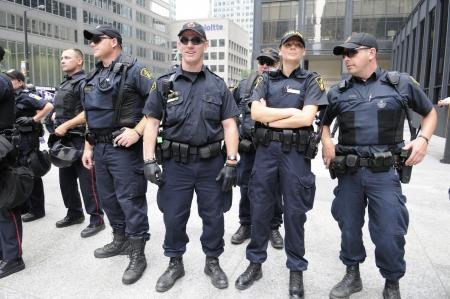 トロント-6 月 27: トロント警察役員のトロント、カナダで 2010 年 6 月 27 日に G20 の抗議の間に主要な金融ビル TD 塔の前で立っています。
