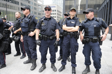 TORONTO-JUNE 27: Toronto police officers standing in front of the TD Tower a major financial building during the G20 Protest on June 27, 2010 in Toronto, Canada. 에디토리얼