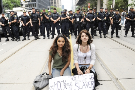 g20: TORONTO-JUNE 27: Two unidentified teens doing a protest by sitting on the streets in front of the barricade of the police officers during the G20 Protest on June 27, 2010 in Toronto, Canada.