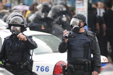 トロント-6 月 26: A トロント警察役員が 2010 年 6 月 26 日に、カナダのトロントでの G20 の抗議の間に将来の参照用ラリーを記録します。