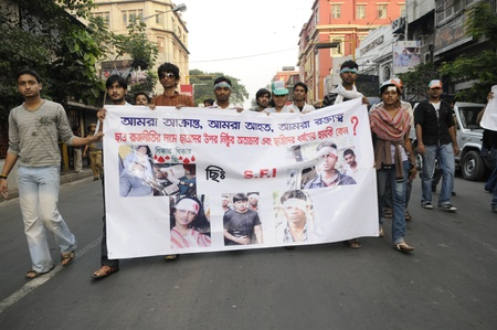 enmity: KOLKATA- DECEMBER 20: Members of the student union walks with a banner with images of the victims of political enmity, during a silent rally in Kolkata, India on December 20, 2010.