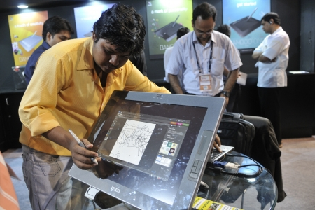 KOLKATA- FEBRUARY 20: A visitor draws on a screen with a cordless touch pen during the Information and Communication Technology (ICT) conference and exhibition in Kolkata, India on February 20,2011.