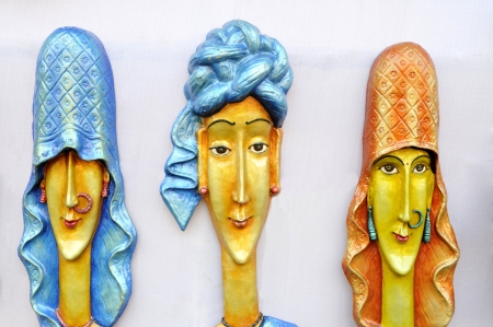 KOLKATA - FEBRUARY 23: Sculptures of men and women hanging on a wooden board during the Handicraft Fair-the biggest of its kind in Asia on February 23, 2011 in Kolkata, India.