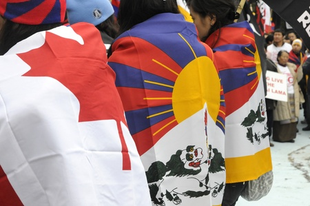 TORONTO - MARCH 10: Tibetans meditating on the streets wrapped in Tibetan flags during a rally organized to protest against the Chinese occupation of Tibet on March 10 2009 in Toronto, Canada.