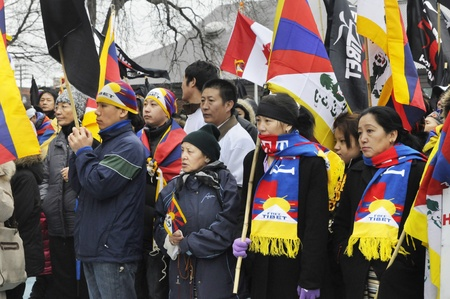 TORONTO - MARCH 10: Tibetans listening to the speakers during a rally organized to protest against the Chinese occupation of Tibet on March 10 2009 in Toronto, Canada.