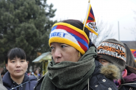 TORONTO - MARCH 10: A Tibetan woman with Tibetan flag colored headband marching in a rally organized to protest against the Chinese occupation of Tibet on March 10 2009 in Toronto, Canada.