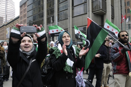 genocide: TORONTO-MARCH 16: Syrians taking pictures and clapping during a protest rally organized to raise awareness and commemorate two years of Syrian revolution on March 16, 2013 in Toronto, Canada. Editorial