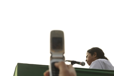 KOLKATA - FEBRUARY 20: A follower taking pictures of Indian Railways minister Ms. Mamata Banerjee speaking to her followers during a political rally organized by her party in Kolkata, India on February 20, 2011.