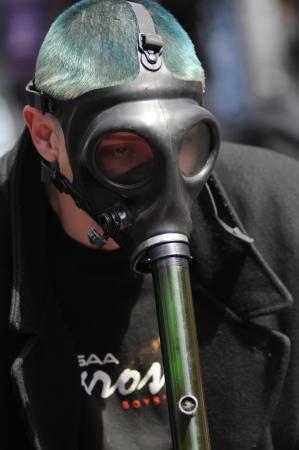 TORONTO - APRIL 20: A masked marijuana smoker smoking from bong during the annual marijuana 420 event at Yonge & Dundas Square on April 20 2012 in Toronto, Canada.