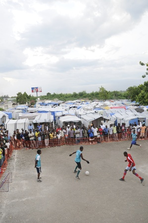 tent city: PORT-AU-PRINCE -AUGUST 26: Residents gathered around a small soccer playground within a tent city to witness a friendly soccer game between two tent cities in Port-Au-Prince,Hait i on August 26, 2010.