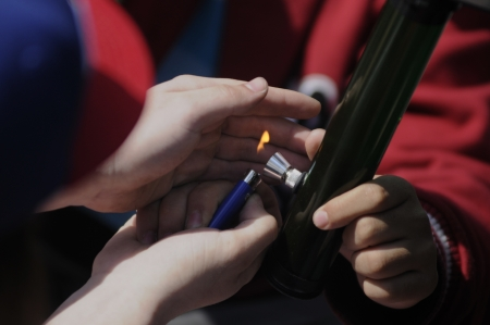 TORONTO - APRIL 20: Human hands lighting and guarding the flame to light a marijuana bong during the annual marijuana 420 event at Yonge & Dundas Square on April 20 2012 in Toronto, Canada.