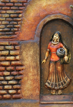 KOLKATA - FEBRUARY 23: Sculpture of a village woman a wooden background during the Handicraft Fair in Kolkata-the biggest of its kind in Asia on February 23, 2011 in Kolkata, India.