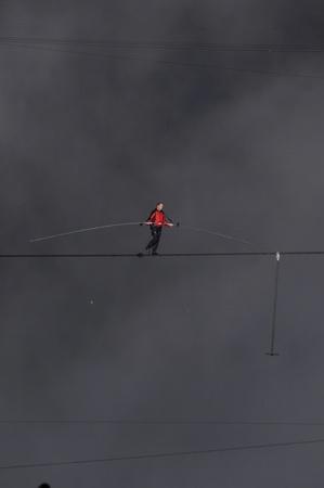 gusty: NIAGARA FALLS -JUNE 15: Nik Wallanda battling gusty wind while crossing the Niagara Falls on a tightrope on June 15 2012 in Niagara Falls, Canada. Editorial