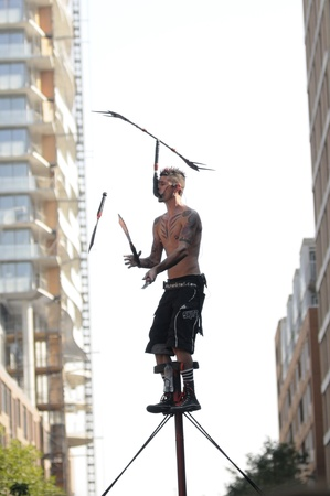 sword act: TORONTO-AUGUST 31: A performer juggling with swords while high up in the air during the Buskerfest Festival on June 31, 2012 in Toronto, Canada.