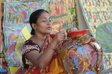 KOLKATA - FEBRUARY 23: A rural woman painting a pot during Handicraft Fairin Kolkata -the biggest of its kind in Asia, on February 23, 2011 in Kolkata, India.