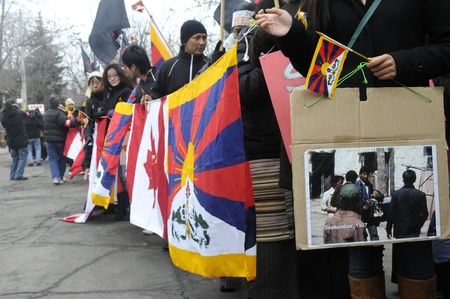 TORONTO - MARCH 10: Tibetans with picture of Chinese atrocities marching in a rally organized to protest against the Chinese occupation of Tibet on March 10 2009 in Toronto, Canada.
