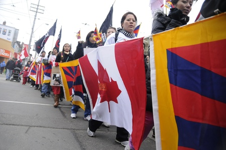 TORONTO - MARCH 10: Tibetans with the flags of Canada and Tibet together marching in a rally organized to protest against the Chinese occupation of Tibet on March 10 2009 in Toronto, Canada.