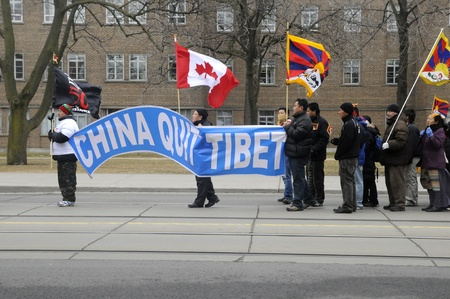 TORONTO - MARCH 10: Canadian Tibetans with a huge banner asking China to quit Tibet marching in a rally organized to protest against the Chinese occupation of Tibet on March 10 2009 in Toronto,Canada.