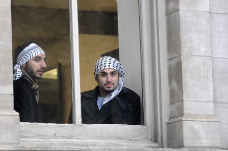 TORONTO - JANUARY 10: Two unidentified Arab youths watching the rally through their window during a rally to condemn the Israel occupation on Gaza on January 10 2009 in Toronto, Canada.