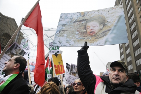 TORONTO - JANUARY 10: A protester holding an image of a child who allegedly was murdered by the Israelis during a rally to condemn the Israel occupation on Gaza on January 10 2009 in Toronto, Canada.