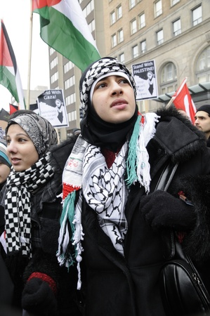 TORONTO - JANUARY 10: Young Arab girls listening to the speakers during a rally to condemn the Israel occupation on Gaza on January 10 2009 in Toronto, Canada.