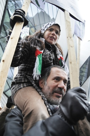 palestinian: TORONTO - JANUARY 10: A small kid with her father during a rally to condemn the Israel occupation on Gaza on January 10 2009 in Toronto, Canada.