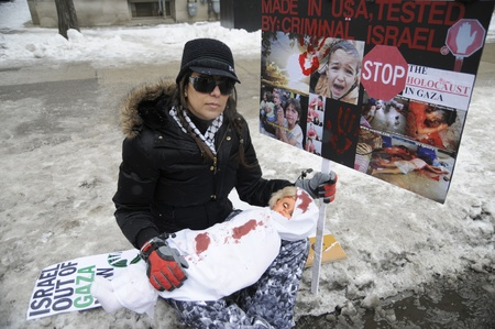 TORONTO - JANUARY 10: A woman sits beside sign denouncing the criminal attitude of America and Israel during a rally to condemn the Israel occupation on Gaza on January 10 2009 in Toronto, Canada.