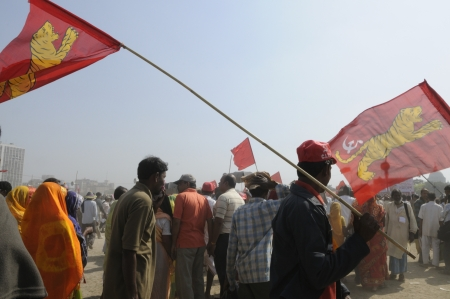 KOLKATA- FEBRUARY 13: Followers carrying flag of All India Forward Bloc a coalition partner in the Government flying, during a political rally in Kolkata, India on February 13, 2011.