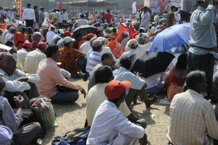 KOLKATA- FEBRUARY 13: People with umbrellas and handkerchiefs to protect themselves from the heat during a political rally in Kolkata, India on February 13, 2011.