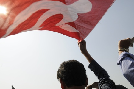 hammer and sickle: KOLKATA- FEBRUARY 13: A communist  follower  waiving the symbol of hammer & sickle flying during a political rally in Kolkata, India on February 13, 2011.
