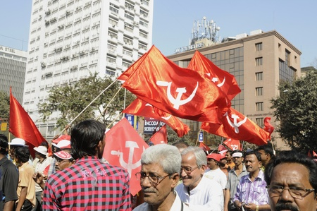 marchers: KOLKATA- FEBRUARY 13: Marchers hoist the communist flags in front of the Tata Center in Kolkata during a political rally in Kolkata, India on February 13, 2011.