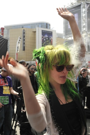 TORONTO - APRIL 20: A marijuana legalization activist dressed all in green dancing during the annual marijuana 420 event at Yonge & Dundas Square on April 20 2012 in Toronto, Canada.