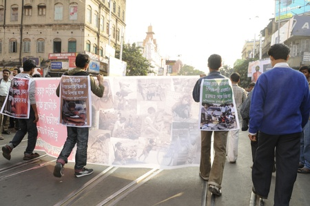 marchers: KOLKATA- DECEMBER 20: Marchers walk along the street with the images of the victims killed during the electoral confrontation during a silent rally in Kolkata, India on December 20, 2010.