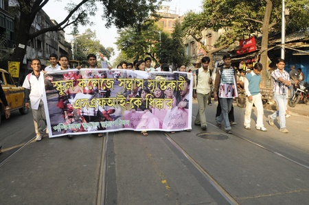 KOLKATA- DECEMBER 20: Silent protesters walking along with a banner denouncing political deaths during a silent rally in Kolkata, India on December 20, 2010.