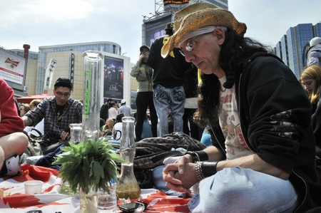 legalization: TORONTO - APRIL 20: A marijuana activist sitting in front of his bong during the annual marijuana 420 event at Yonge & Dundas Square on April 20 2012 in Toronto, Canada.