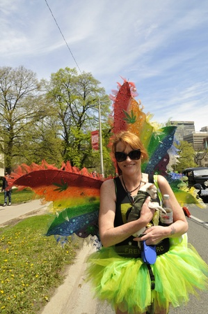 TORONTO-MAY 5: A Marijuana legalization supporter with green dress and butterfly wings along with her puppy participating in the 14th annual Global Marijuana March on May 5 2012 in Toronto, Canada.