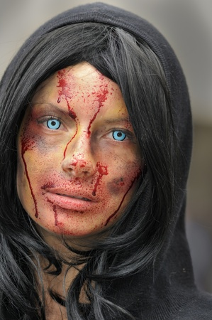 TORONTO-OCTOBER 20: A participant with Zombie contact lenses and fake blood dropping from her face during the Halloween parade on October 20, 2012 in Toronto, Canada.