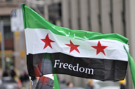 TORONTO-MARCH 16: A protester waiving a Syrian flag during a protest rally organized to raise awareness and commemorate two years of Syrian revolution on March 16, 2013 in Toronto, Canada.