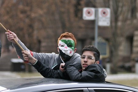 TORONTO-MARCH 16: Unidentified young Syrians waiving Syrian flag from inside a car during a protest rally organized to commemorate two years of Syrian revolution on March 16, 2013 in Toronto, Canada.